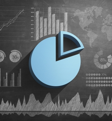 light blue pie graph on top of chalkboard background with other graphs and charts.