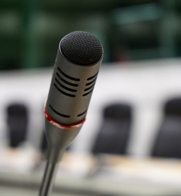 Microphone in focus with conference room chairs in background out of focus