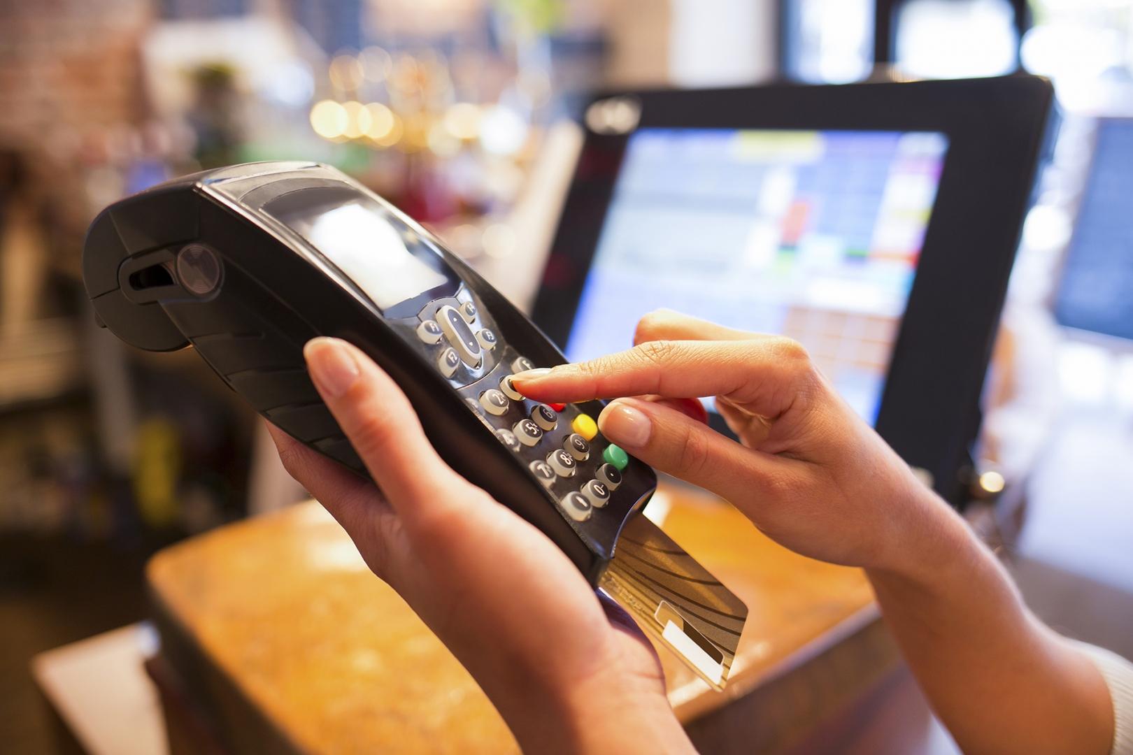 A shopper keys in their debit card code in a retail store