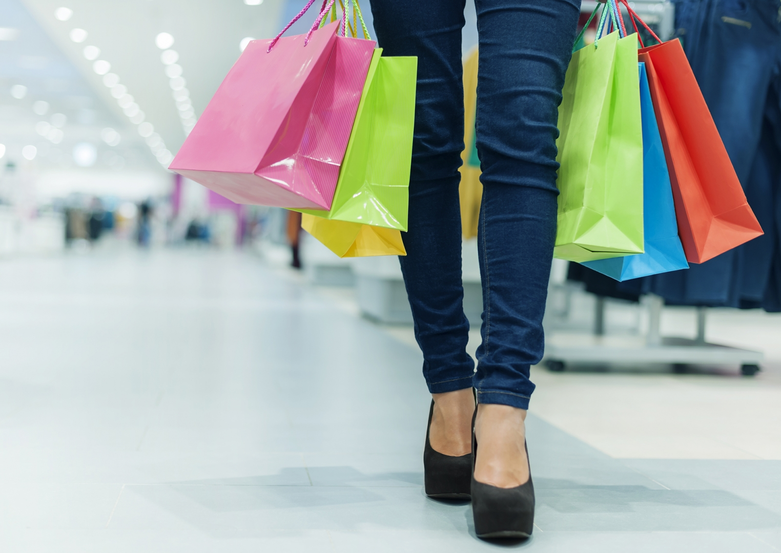 image of bottom half of woman walking through mall carrying shopping bags