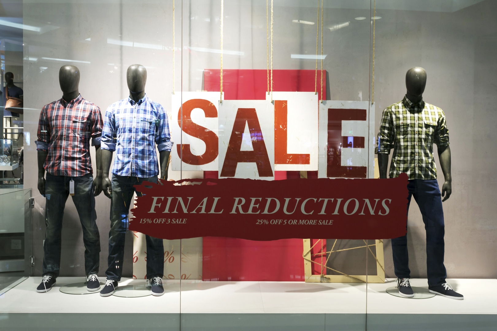 apparel store window with sale advertised in display