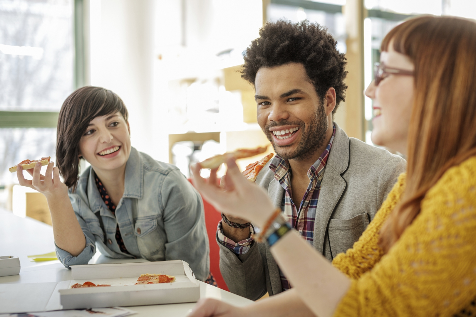 millennials enjoying pizza at a fast casual restaurant