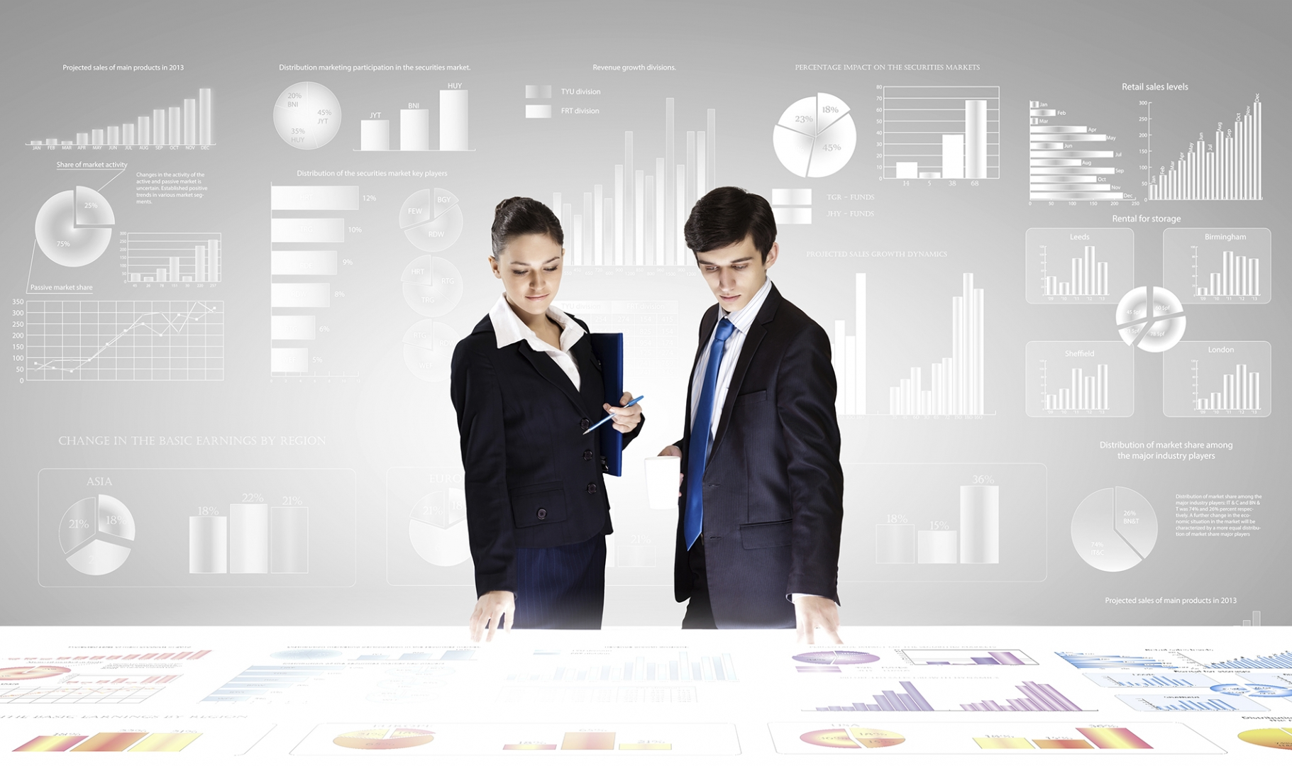 two business professionals overlooking large table filled with graphs and charts