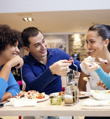 three people enjoying a meal at a restaurant
