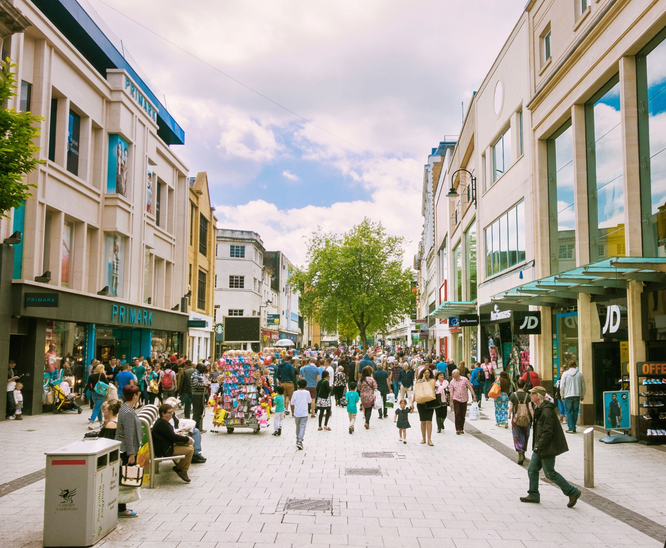 wide angle view of a city street with filled with pedestrians visiting retailers