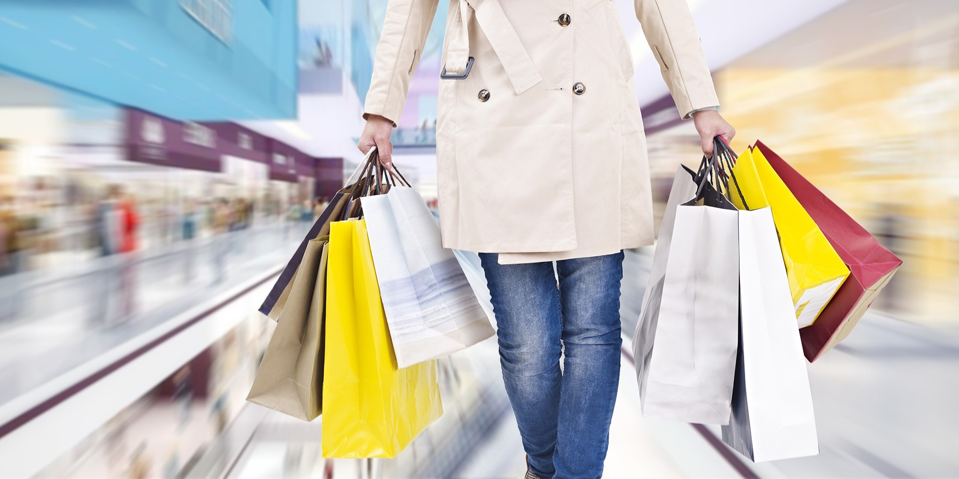 woman carrying two handfuls of shopping bags while walking through store.