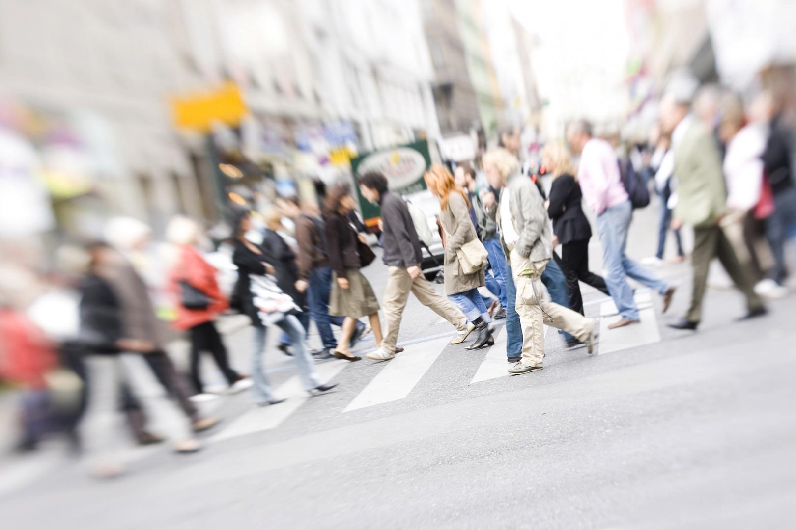people walking across a cross walk on a busy street