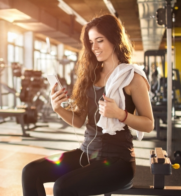 woman sitting on workout bench at gym
