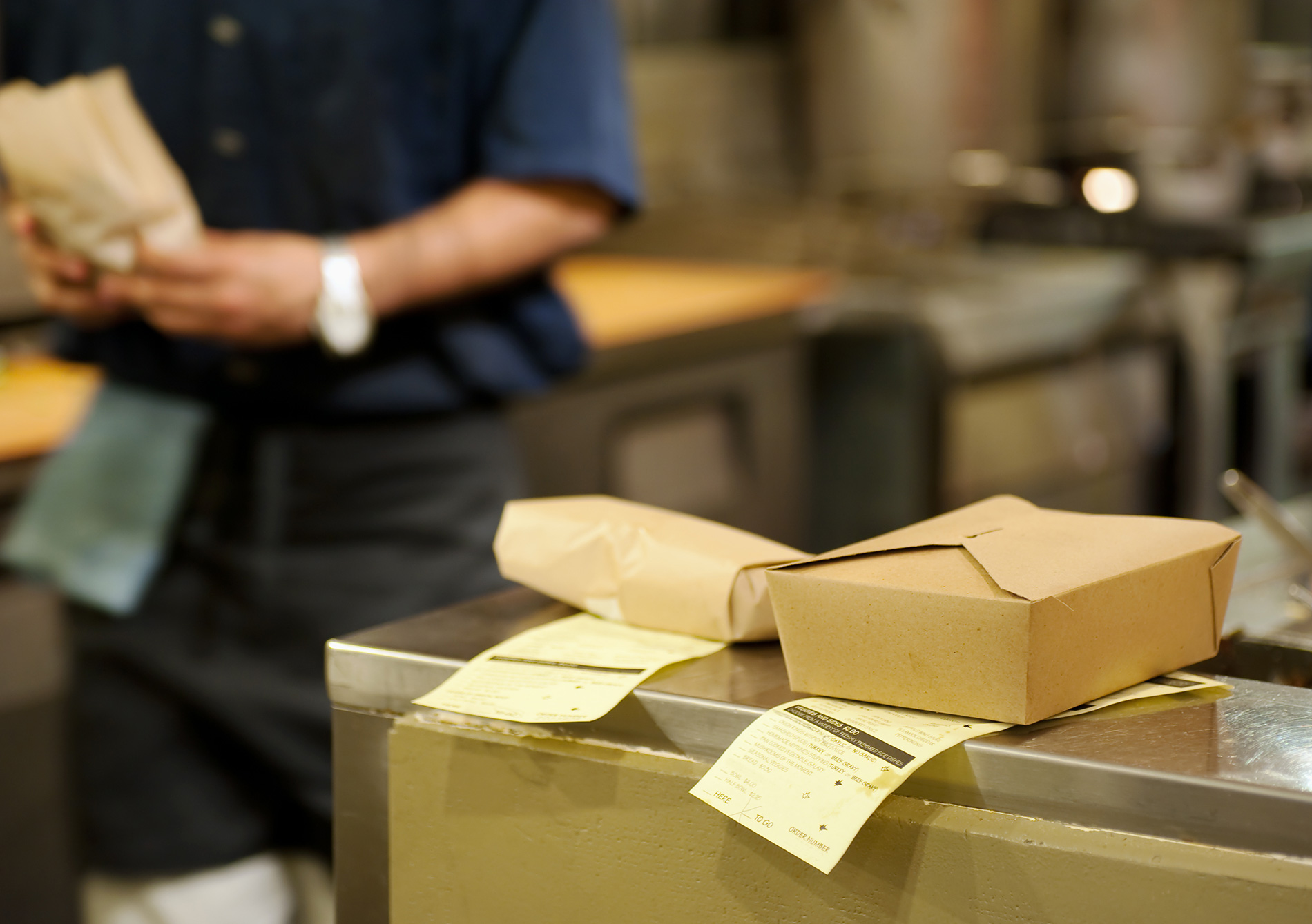 waiter prepares online food order for takeout