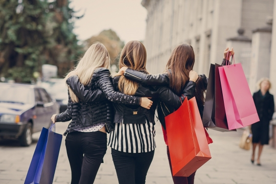 female shoppers walking side by side after shopping trip