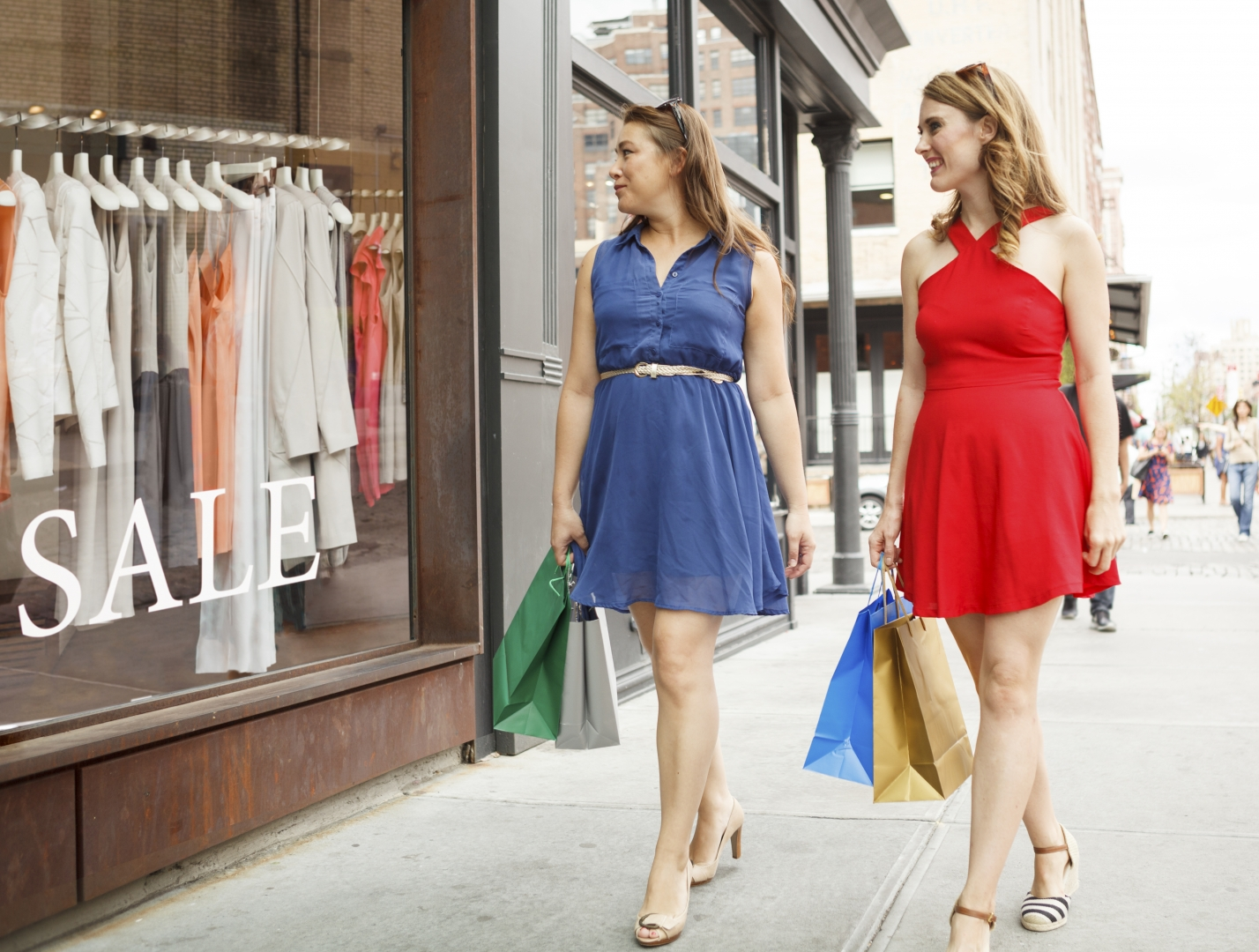 two women carrying shopping bags outside of apparel store