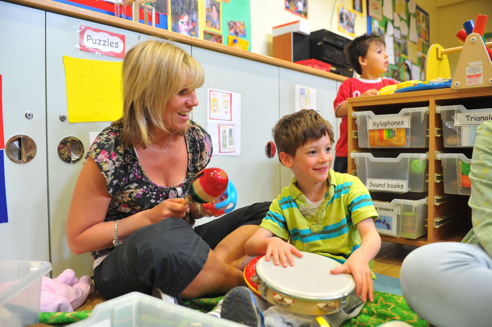child and parent playing musical instruments at group class