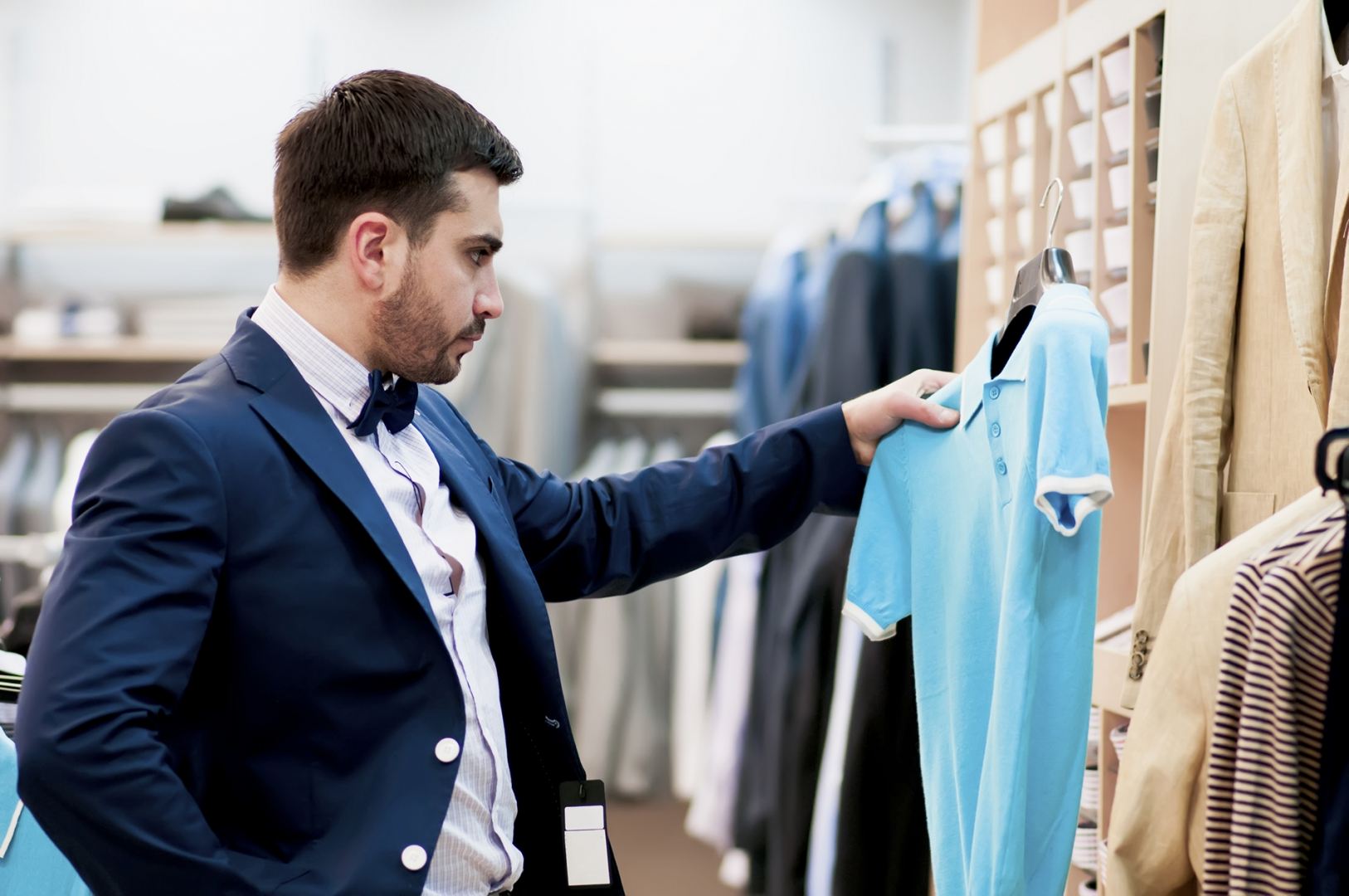 businessman looking through shirts at a retail store