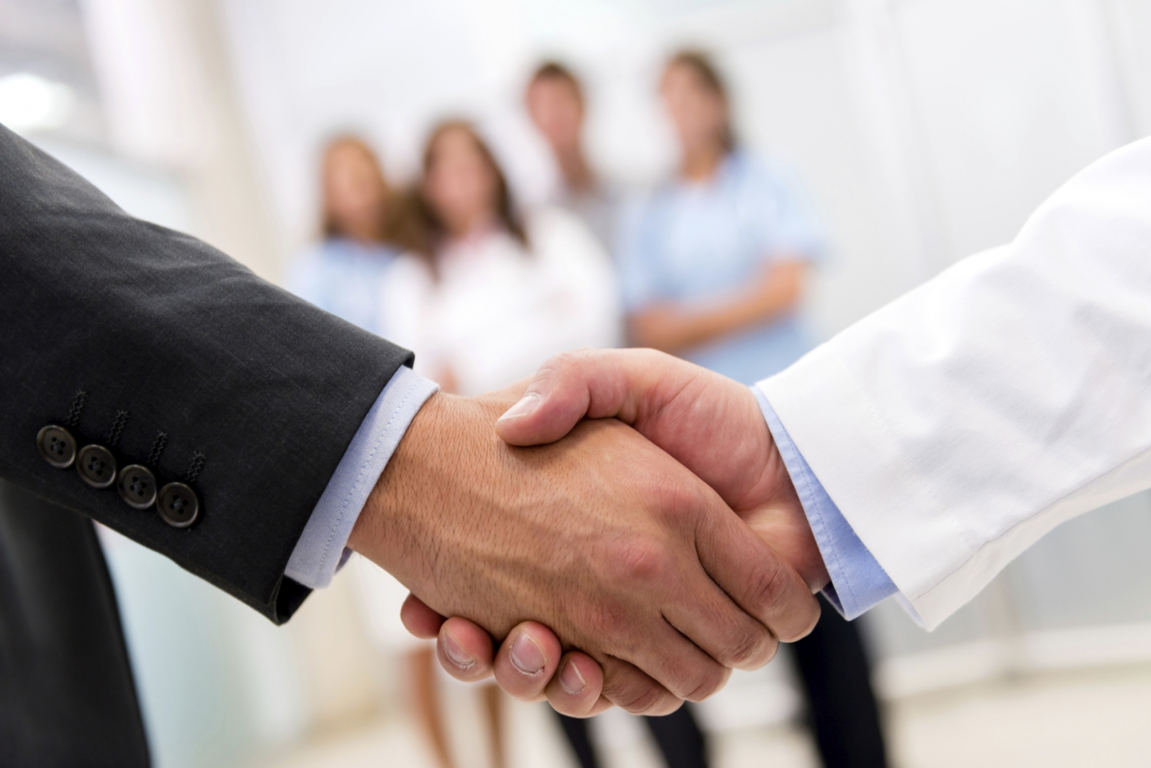 business people shaking hands with faded image of people in the background