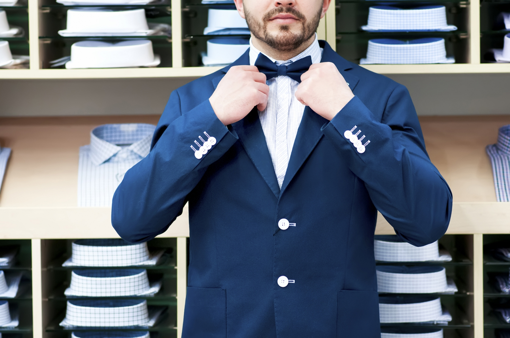 man trying on suit and tying tie