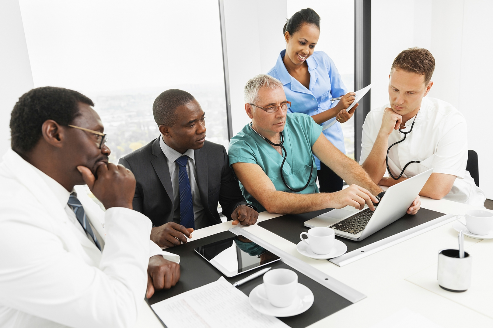business people and doctors around a table reviewing documents