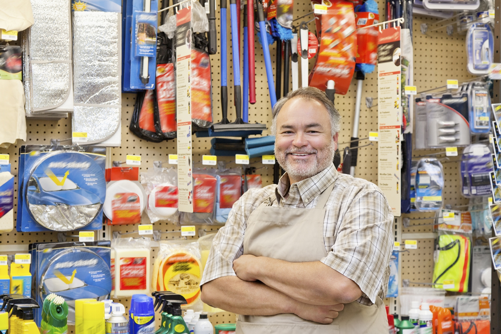 A store owner stands proudly in his store