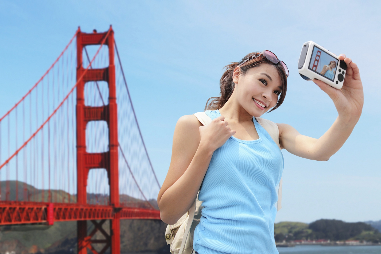 A tourist takes a picture in front of the Golden Gate Bridge