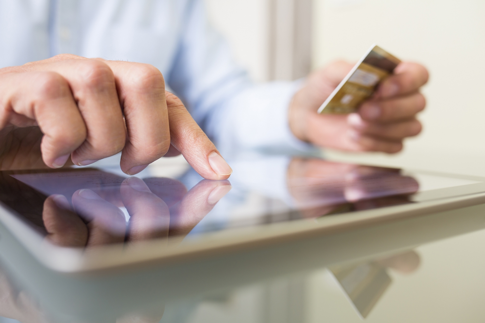 partial image of person making purchase with a tablet