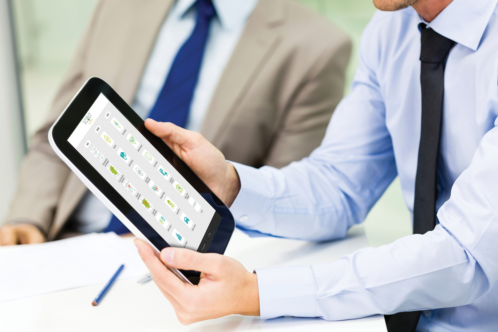 business person showing colleague something on a tablet screen